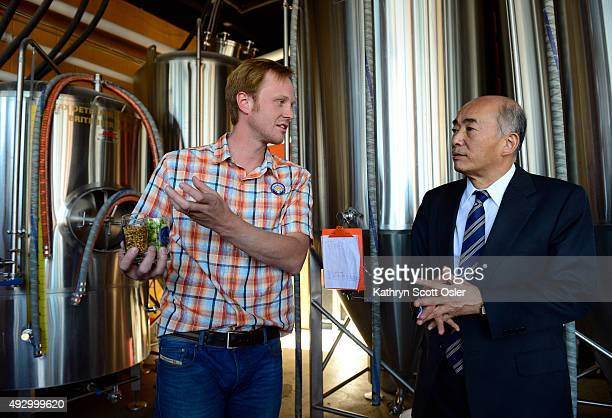 Cofounder of the Denver Beer Company Charlie Berger left shows Japanese Ambassador Kenichiro Sasae some of the key ingredients to their beer while on...
