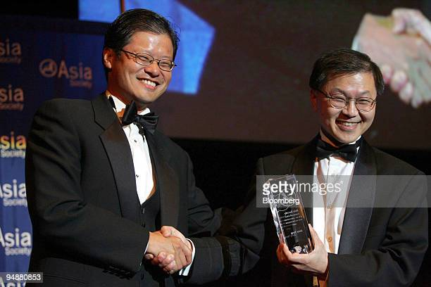 CoFounder of Yahoo Jerry Yang left receives his award as an Outstanding Asian American Entrepreneur from Dr David Ho Director of the Aaron Diamond...