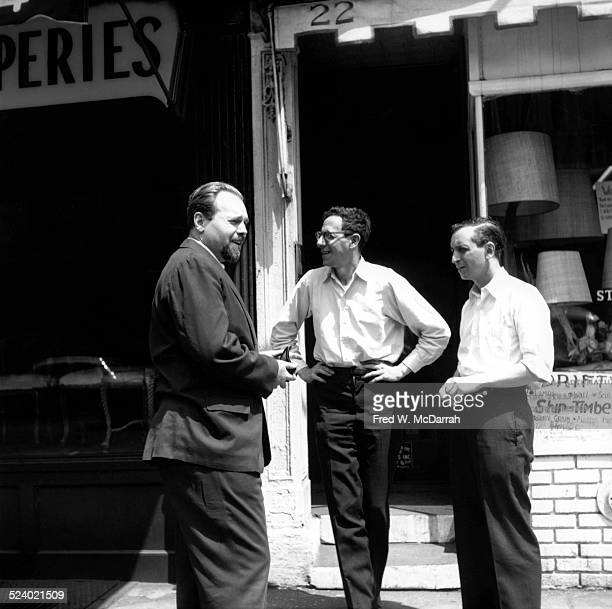 Cofounders of the Village Voice newspaper Edwin Fancher and Dan Wolf stand with Jerry Tallmer on the sidewalk in front of the paper's first offices...