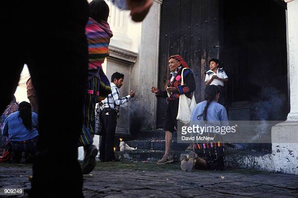 A cofradia one of the religious and social leaders of the Maya community leaves the church in Chichicastenango as other Indians pray and burn incense...