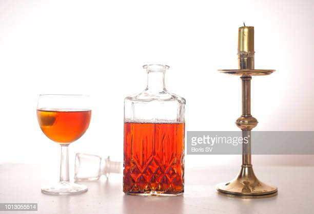 cognac bottle and brass candlestick - liqueur stock pictures, royalty-free photos & images