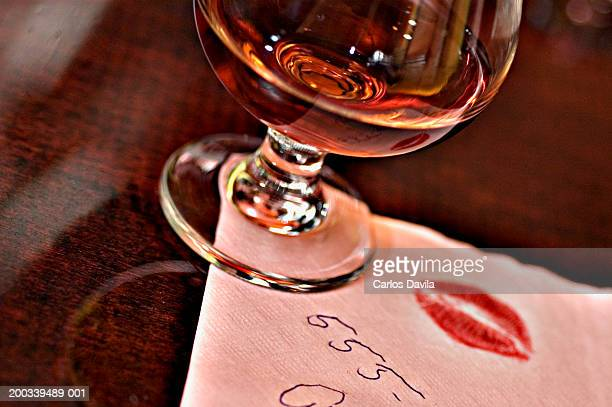 cognac glass on napkin with telephone number and kiss imprint - telephone number stock pictures, royalty-free photos & images