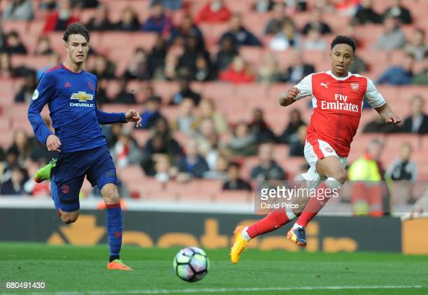 Cohen Bramall of Arsenal crosses the ball as Callum Gribbin of Man Utd closes in during the Premier League 2 match between Arsenal U23 and Manchester...
