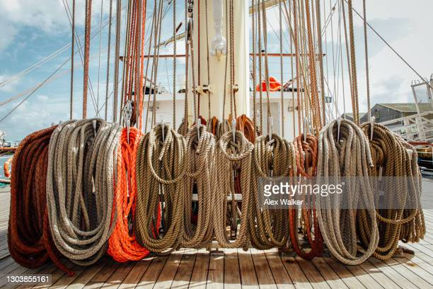 coiled rope at the base of the mast on a large sailing ship. - falmouth england stock pictures, royalty-free photos & images