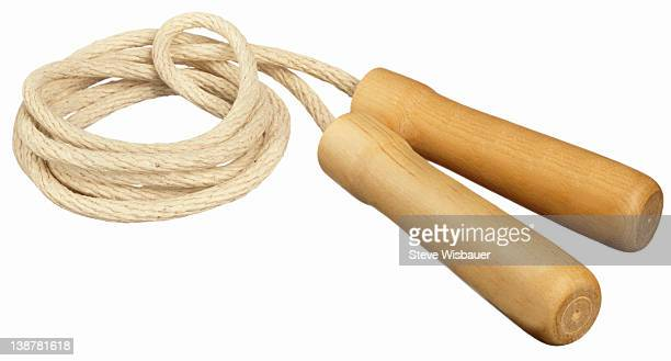A coiled up classic jump rope with wood handles