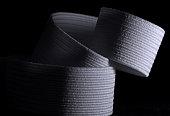 Coiled white elastic set against black background