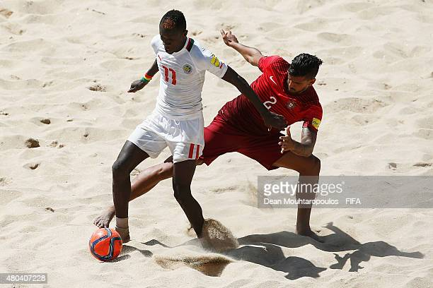 Coimbra of Portugal battles for the ball with Ibrahima Balde of Senegal during the Group A FIFA Beach Soccer World Cup match between Senegal and...