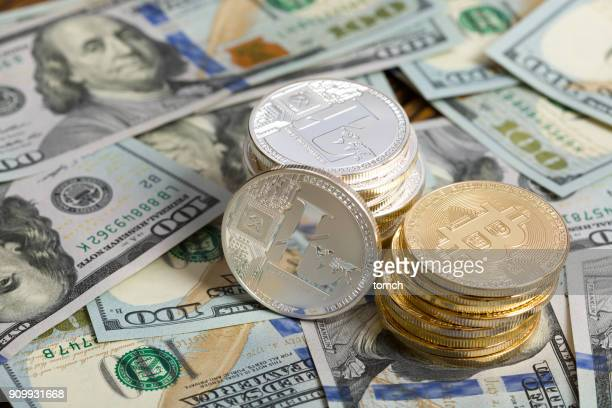 Coin in shape of cryptocurrency bitcoin and litecoin on top of US dollars. Bitcoin and litecoin are a digital coins, on photo are physical representation of bitcoin and litecoin.