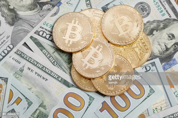 Coin in shape of cryptocurrency bitcoin on top of US dollars. Bitcoin is a digital coin, on photo is physical representation of bitcoin.