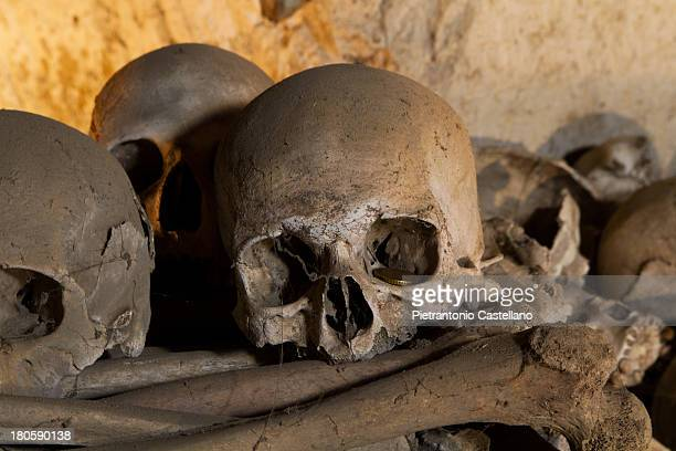 """Coin left in the eye socket of a skull in the Fontanelle Ossuary in Naples, Italy. The cult of the """"dead's heads"""" in Naples has extremely ancient..."""