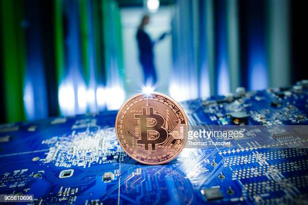 A coin of the cryptocurrency Bitcoin stand on a circuit board of a computer in front of server racks in a server center on January 12 in Berlin...