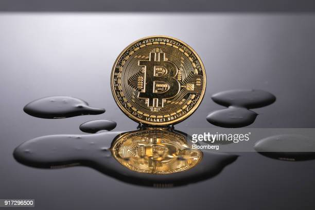 A coin representing Bitcoin cryptocurrency is reflected on a polished surface as it sits in a pool of translucent liquid in this arranged photograph...