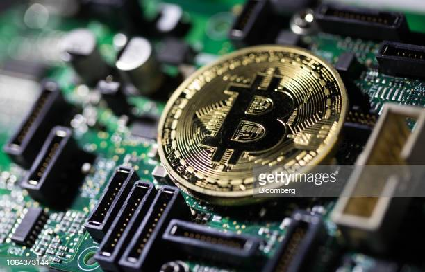 Coin representing Bitcoin cryptocurrency sits on a computer circuit board in this arranged photograph in London, U.K., on Tuesday, Feb. 6, 2018. The...