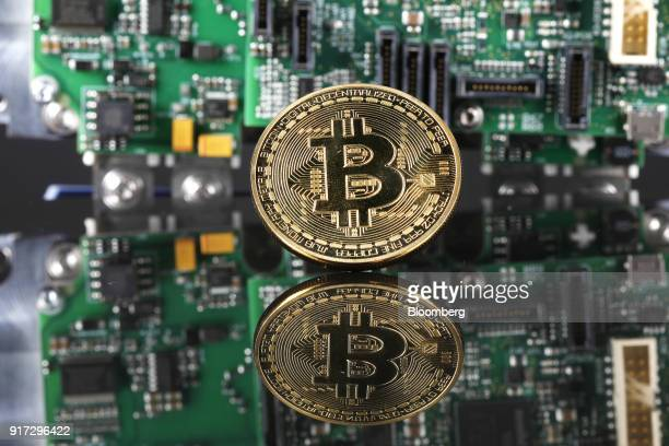 A coin representing Bitcoin cryptocurrency sits reflected on a polished surface and photographed against a computer circuit board in this arranged...
