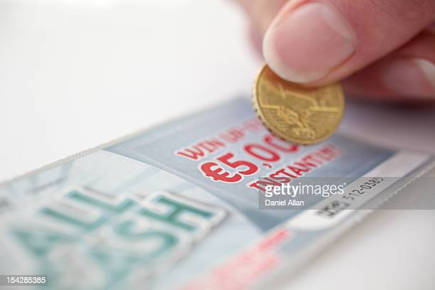 Coin scratching a lottery scratch card