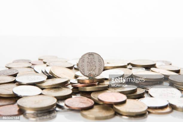 A coin stands on a pile of coins
