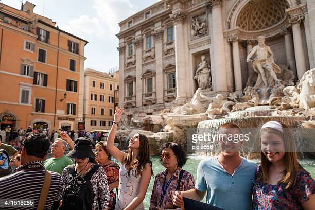 coin throwing in trevi fountain, rome - trevi fountain stock photos and pictures