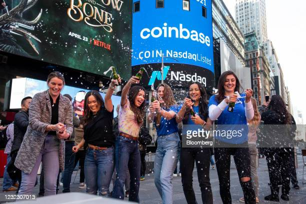 Coinbase employees spray champagne during the company's initial public offering outside the Nasdaq MarketSite in New York, U.S., on Wednesday, April...