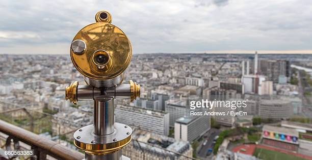 Coin-Operated Binocular By Cityscape Against Sky