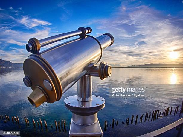 Coin-Operated Binocular On Railing Against Lake During Sunset