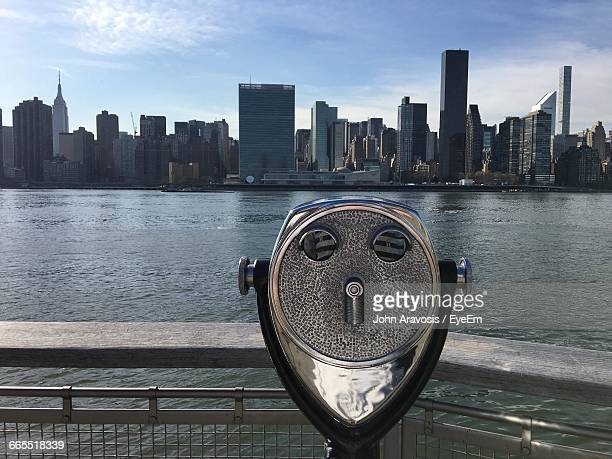 Coin-Operated Binoculars By River And City Skyline Against Sky