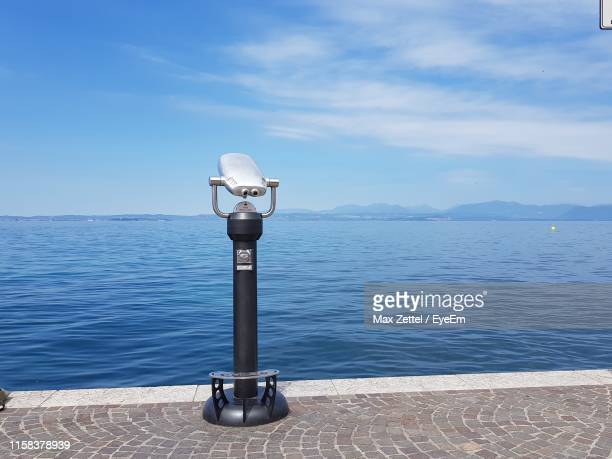coin-operated binoculars by sea against sky - binoculars stock pictures, royalty-free photos & images