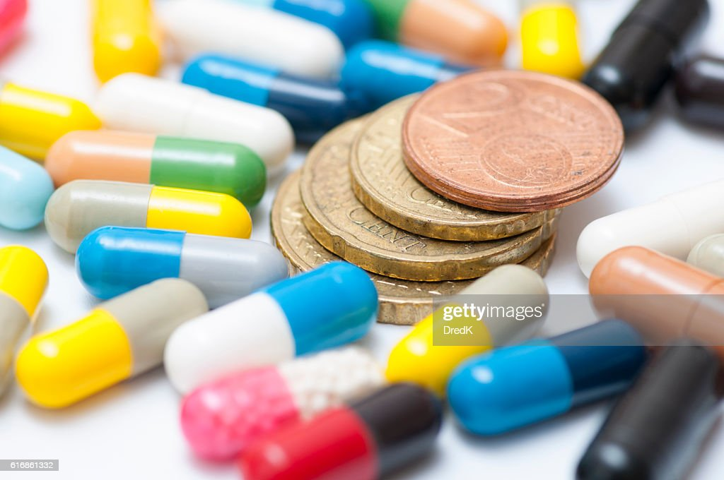 Coins among various drugs (capsules and pills) : Stock Photo