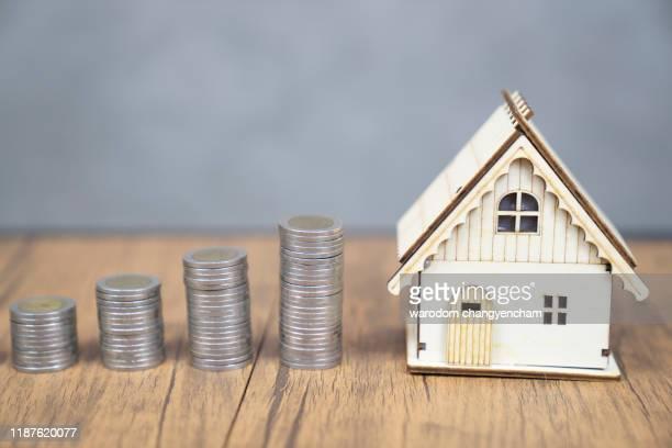 coins arranged with the paper house. saving concept. - erschwinglich stock-fotos und bilder