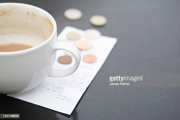 Coins by coffee cup and bill