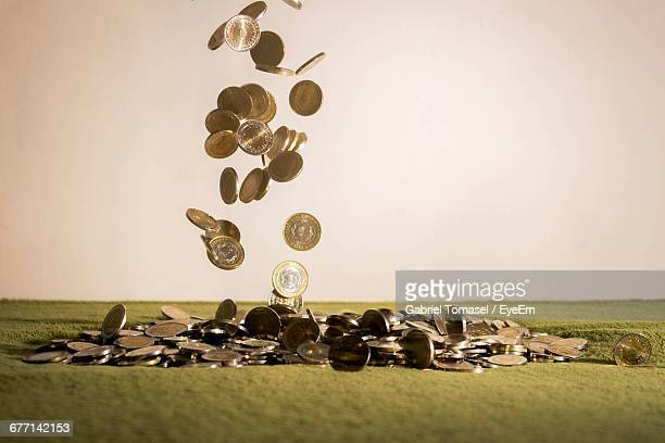 Coins Falling On Green Table Against White Background