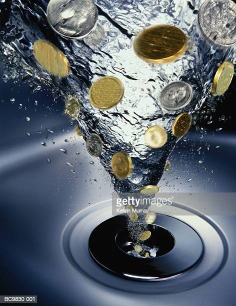 Coins going down drain in vortex of water (Digital Composite)
