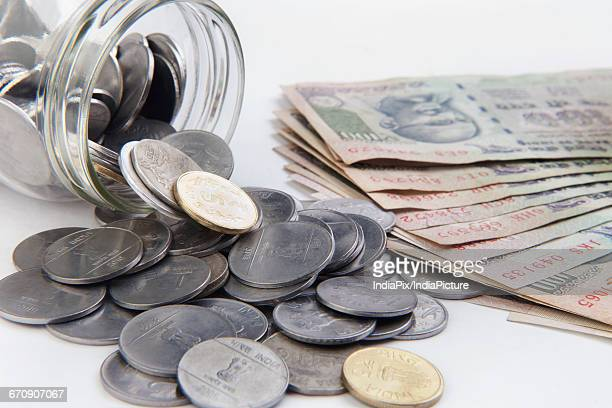 coins in a mason jar over white background