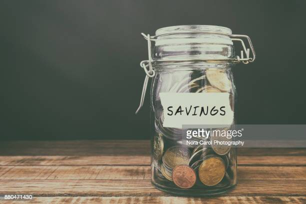 coins in jar with text savings - piggy bank stock photos and pictures