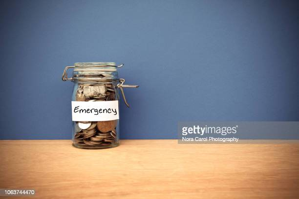 coins jar for emergency savings - emergencies and disasters stock pictures, royalty-free photos & images