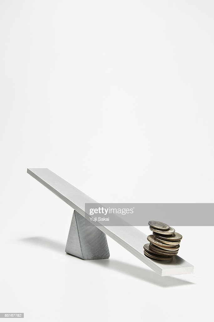 coins on the seesaw : Stock Photo