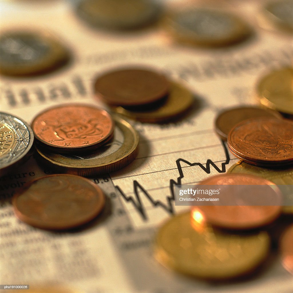 Coins on top of financial charts. : Stockfoto