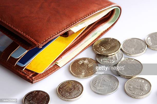 Coins scattered beside a wallet