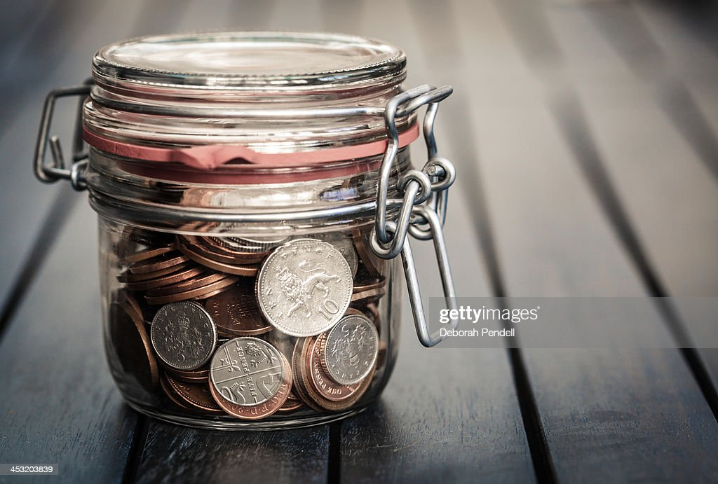 Coins secured in glass jar : Stock Photo