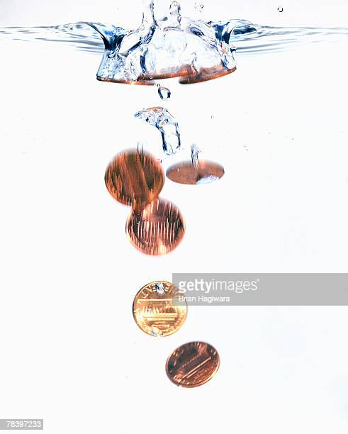 Coins sinking in water