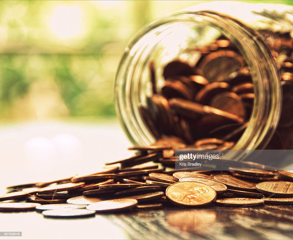 Coins spilled from jar : Bildbanksbilder