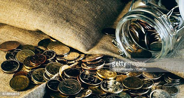 Coins Spilling From Glass Jar On Fabric