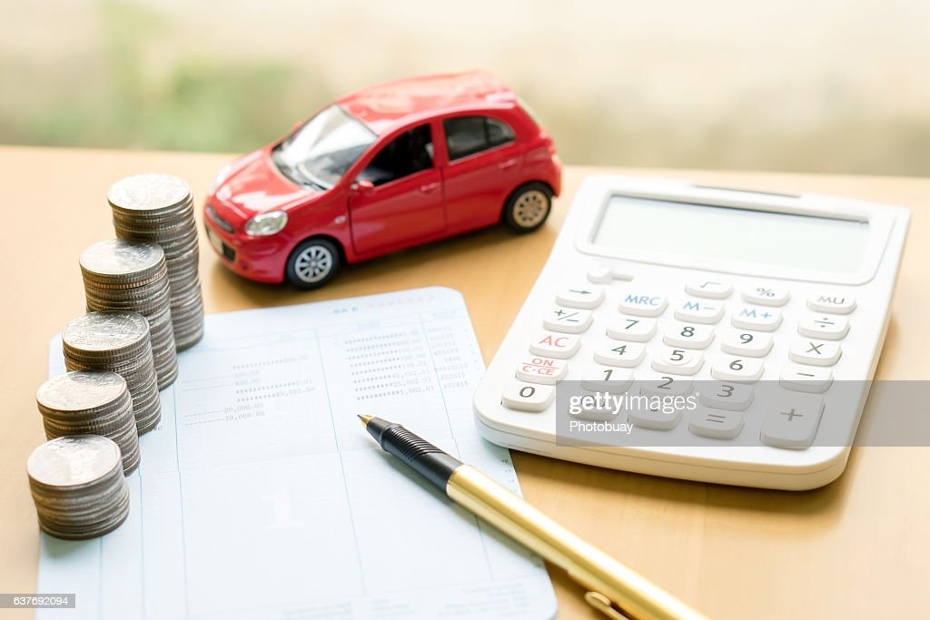 Coins stack in columns on saving book and car : Photo