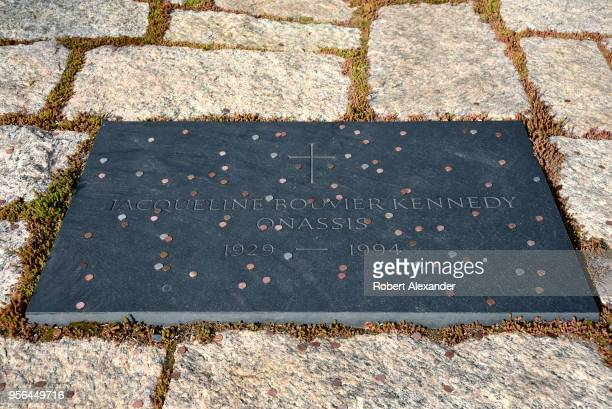 Coins tossed by visitors litter the grave of former First Lady Jacqueline Kennedy Onassis at Arlington National Cemetery near Washington DC