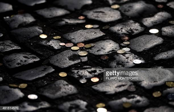 Coins usually thrown by tourists to make a wish are seen on the cobbles at the restoration site of the famous Trevi fountain on June 30 2014 in Rome...