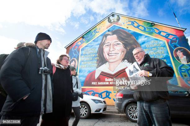Coiste guide Peadar Whelan talks to his group of tourists in front of a mural to of IRA hunger striker Bobby Sands during a political guided tour in...
