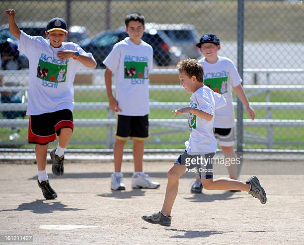 DENVER COJacob Sykora 7yearsold crosses home plate to the delight of his teammates during the 3rd annual McKaila Ball a kickball party at the...
