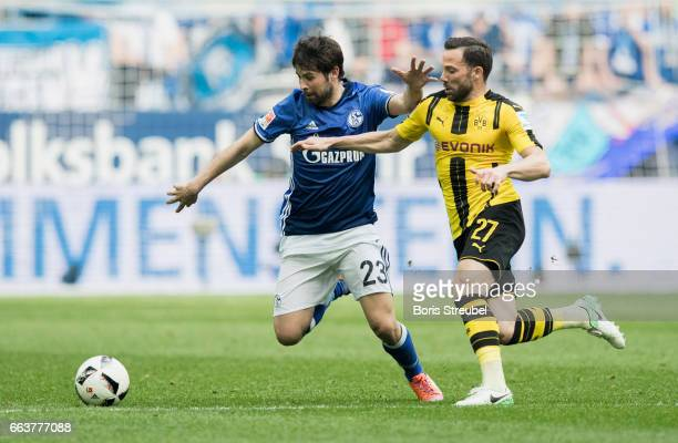 Coke of FC Schalke 04 is challenged by Gonzalo Castro of Borussia Dortmund during the Bundesliga match between FC Schalke 04 and Borussia Dortmund at...