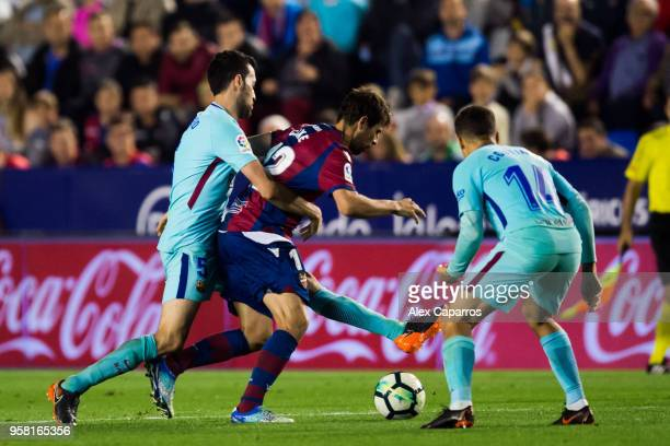 Coke of Levante UD conducts the ball under pressure from Sergio Busquets and Philippe Coutinho of FC Barcelona during the La Liga match between...