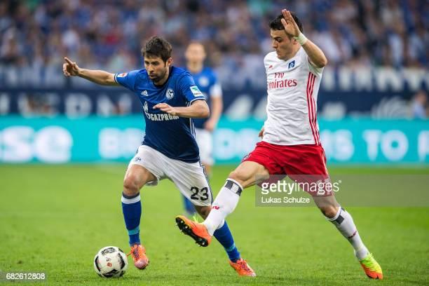 Coke of Schalke and Filip Kostic of Hamburg fight for the ball during the Bundesliga match between FC Schalke 04 and Hamburger SV at VeltinsArena on...
