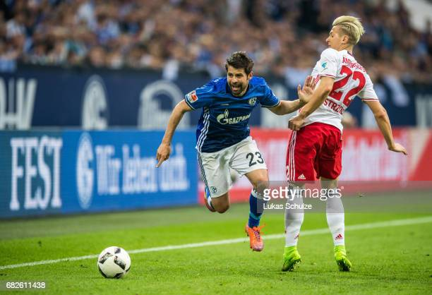Coke of Schalke and Matthias Ostrzolek of Hamburg fight for the ball during the Bundesliga match between FC Schalke 04 and Hamburger SV at...